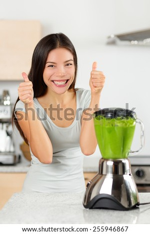 Vegetable smoothie woman happy thumbs up blending green smoothies with blender home in kitchen. Healthy eating lifestyle concept portrait of beautiful young woman preparing drink with spinach etc - stock photo