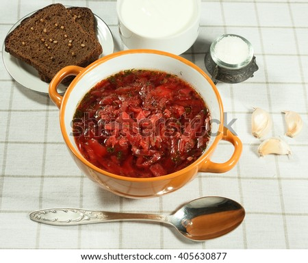 Vegetable soup (borscht).  Traditional Ukrainian soup with fresh vegetables with sour cream. Rye bread, garlic, salt and spoon. Serving on white tablecloth. - stock photo