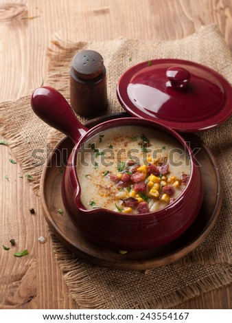 Vegetable soup with corn in pot on wooden background, selective focus - stock photo
