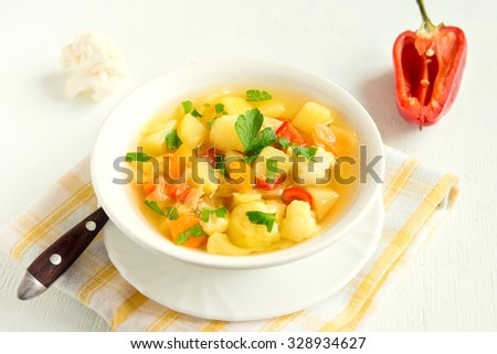 Vegetable soup with ingredients carrot cauliflower potato parsley pepper cabbage tomato close up - stock photo
