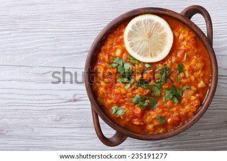 vegetable soup with red lentils and tomatoes close-up on the table. horizontal view from above