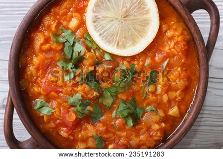 vegetable soup with red lentils and tomatoes macro on the table. horizontal view from above