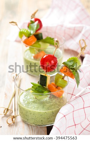 Vegetable sticks and green cold soup (gazpacho) . Focus on soup.  - stock photo