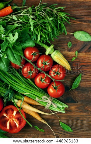 Vegetable summer background. Ripe juicy tomatoes, thyme, zucchini flower, basil leaves and other herbs and greens on brown wooden board. Vegan, vegetarian concept - stock photo