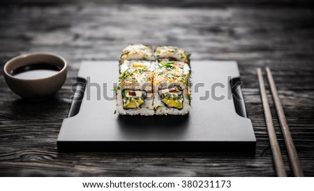 vegetable sushi rolls on black tray with soy and chopsticks - stock photo