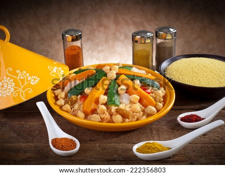Vegetable tagine with cous cous and spices on wooden table. - stock photo