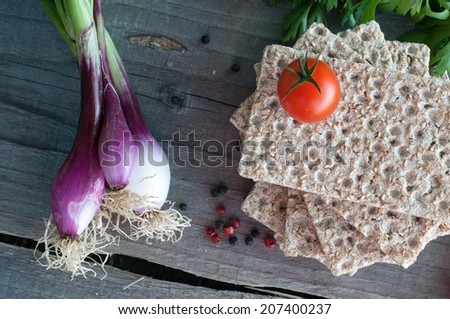 Vegetables and crisp bread on wooden table - stock photo