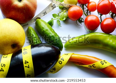 vegetables and fruits for weight loss, a measuring tape, diet, weight loss,cherry tomatoes, green peppers.cucumber.eggplant - stock photo