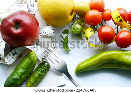 vegetables and fruits for weight loss, a measuring tape, diet, weight loss. red Apple , cucumber,peppers,tomatoes ,yellow pear,Notepad, fork - stock photo