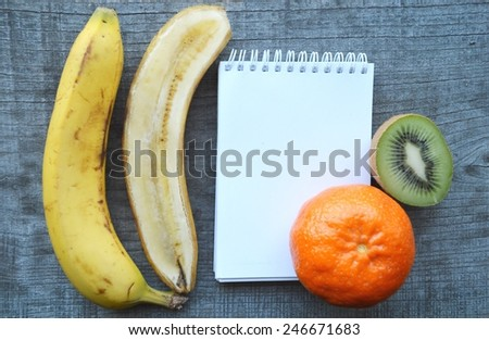 vegetables and fruits for weight loss, diet, weight loss,notebook, diary, orange, tangerine, banana, kiwi - stock photo