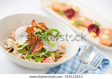 Vegetables and fruits salad with balsamic vinegar and navel orange dressing and smoked striploin ham 1.5 millimeters thickness in ceramic bowl, a modern cusine concept food - stock photo