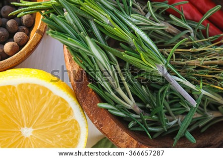 Vegetables and herbs as ingredients for chicken dish recipe: rosemary, lemon, allspice, thyme and chili pepper in round  plates - stock photo