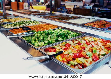 Vegetables and other foods in free-flo restaurant, toned image - stock photo