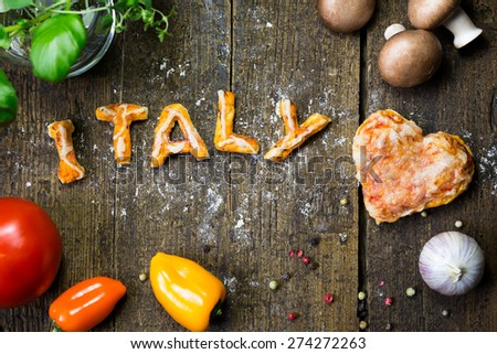 Vegetables and spices on wood, pizza, heart and word Italy - stock photo