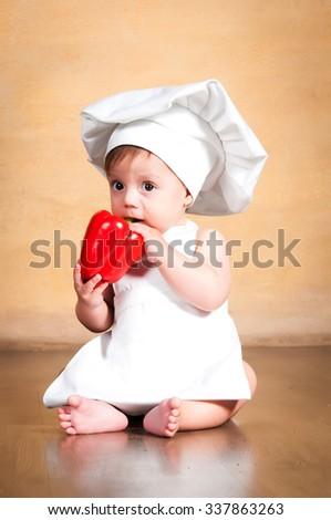 Vegetables are good for health. little cook in a chef's hat eating fresh red paprika - stock photo