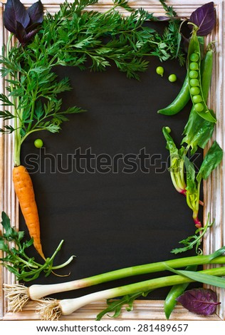 Vegetables garden frame with copy space for text. Fresh carrot, garlic, basil, arugula and green peas. - stock photo