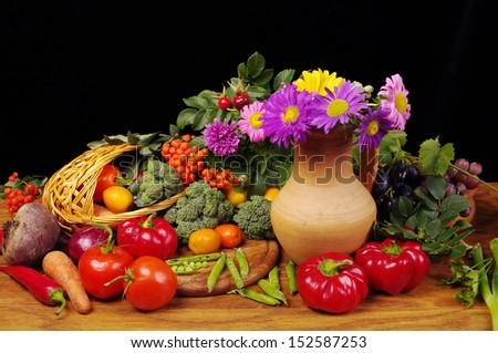 Vegetables, grapes and flowers. Isolated on black    - stock photo