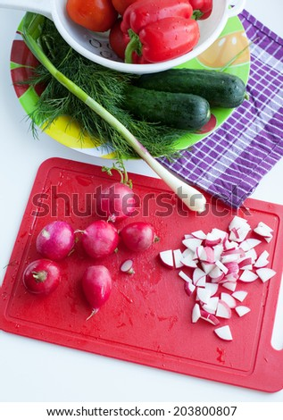 Vegetables in bowl , chopped radish on background of red chopping board, isolated on white - stock photo