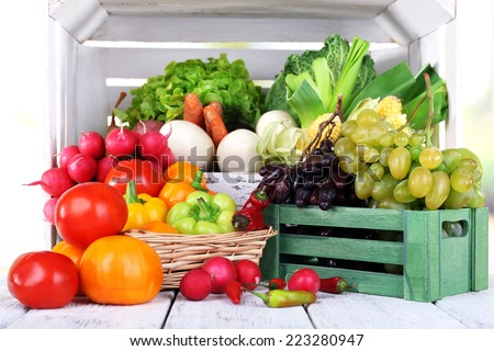 Vegetables in crate and in basket on white wooden box background - stock photo