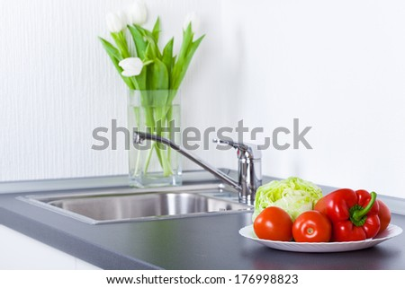 Vegetables in plate on worktop, in the kitchen - stock photo
