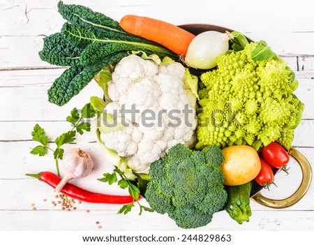 Vegetables in pot on white rustic background.Winter veggies.Healthy cooking concept. - stock photo