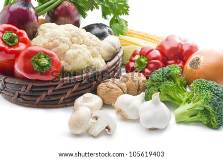 Vegetables. Mix of fresh ripe vegetables arranged in a wicker basket and around close-up  isolated on white background - stock photo