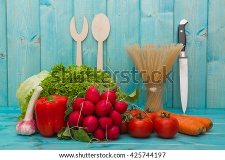 vegetables mix : some raw ripe fresh tomatoes, carrots, garlic,radishes, carrots, peppers, lettuce and cabbage over blue table, photo with depth of field - stock photo