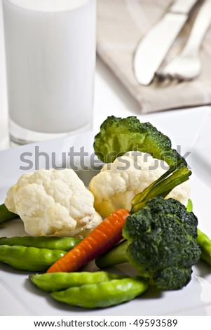 Vegetables On Plate With Glass Of Milk And Cutlery - stock photo