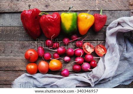 Vegetables on vintage wood background - autumn harvest. Fresh vegetable on wooden table. Top view. Autumn harvest:  radishes, tomatoes, peppers . Autumn background. Ripe vegetables. - stock photo