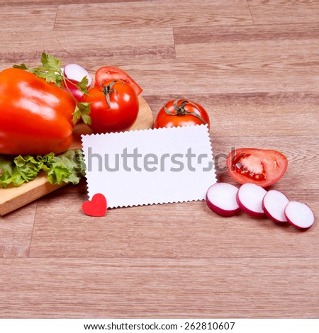 Vegetables on wooden cutting board with paper for text - stock photo