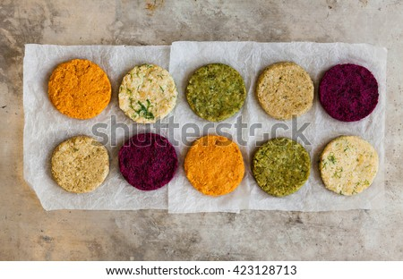 Vegetables patties or cutlets for vegan burgers on a white paper over metal table. A mix stack fresh burgers. Top view.   - stock photo