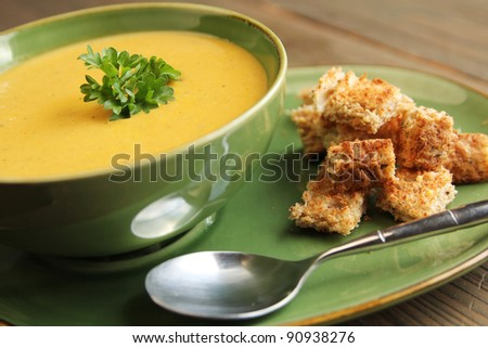 Vegetables soup with bread and spoon on a wooden table - stock photo