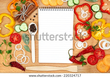 Vegetables, spices and notepad for recipes, on wooden table. - stock photo