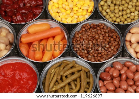 Vegetables such as carrots, lentils, corn, peas and tomatoes in cans - stock photo