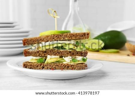Vegetarian avocado sandwich on dark rye bread on white plate - stock photo