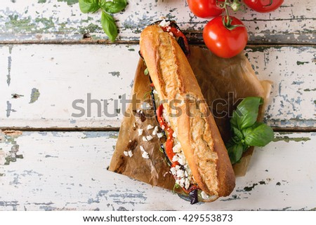Vegetarian baguette submarine sandwich with grilled eggplant, pepper and feta cheese served on baking paper with tomatoes and olive oil over old white wooden background. Top view - stock photo