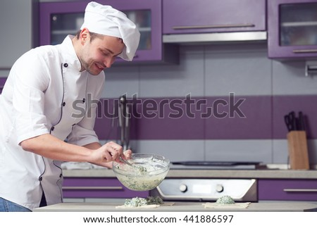 Vegetarian bakery concept. Chef cook putting filler made of spinach and soft feta cheese on slices of puff pastry - french chausson. Modern kitchen in restaurant, cafe. Indoor shot - stock photo