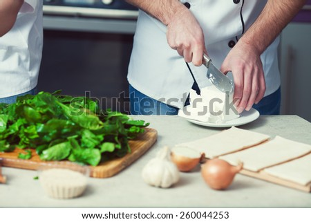 Vegetarian bakery concept. Chef's hands cutting feta cheese, spinach salad in kitchen of cafe, restaurant. Close up. Indoor shot - stock photo