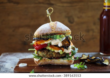 Vegetarian burger made of mushrooms, chickpeas and broccoli with roast pepper, aubergines, rocket leaves and avocado mash - stock photo