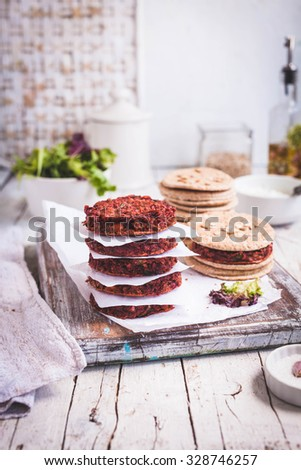 Vegetarian burger with beetroot, chickpeas and quinoa ready to prepare wholegrain hamburger. Rustic neutral style. See series. - stock photo