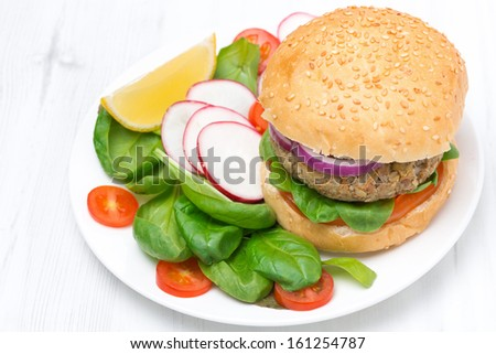 vegetarian burger with fresh salad on the plate, top view, close-up - stock photo