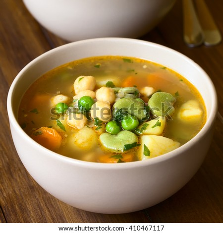 Vegetarian chickpea soup or stew with carrot, broad bean (fava bean), pea, potato, onion, garlic and parsley, photographed with natural light (Selective Focus, Focus in the middle of the first soup) - stock photo