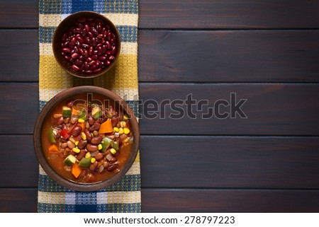 Vegetarian chili dish made of kidney bean, carrot, zucchini, bell pepper, sweet corn, tomato, onion, garlic in bowl, raw kidney beans above, photographed overhead on dark wood with natural light - stock photo