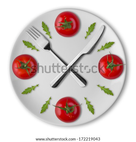 Vegetarian clock concept. Plate with tomatoes, knife and fork - stock photo