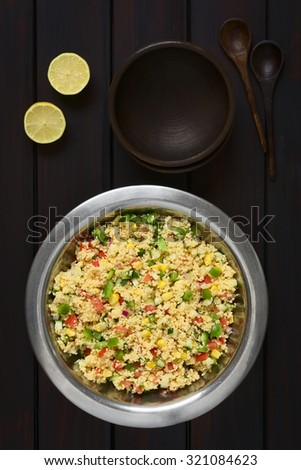 Vegetarian couscous salad with bell pepper, tomato, cucumber, red onion, sweet corn kernels, served in salad bowl. Photographed overhead on dark wood with natural light. - stock photo