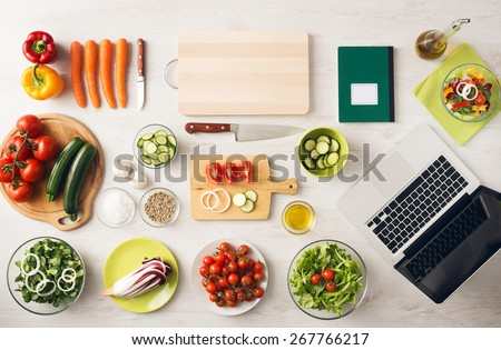 Vegetarian creative cooking at home with kitchen utensils, food ingredients and fresh vegetables on a wooden table, top view - stock photo