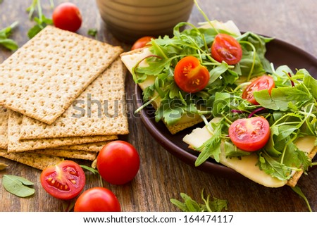 Vegetarian crispbread  with tomatos, cheese and salad mix on the clay plate - stock photo