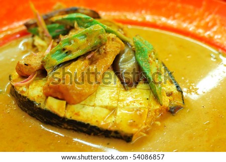 Vegetarian fish curry cooked Asian style. Ingredients include lady fingers and tomatoes. Suitable for food and beverage, healthy lifestyle, and diet and nutrition. - stock photo