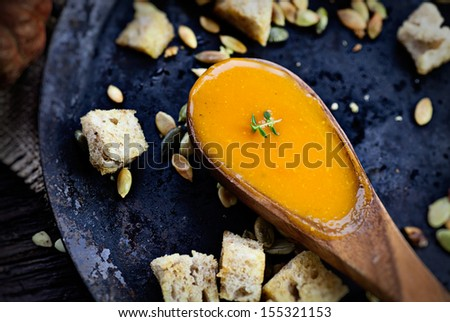 Vegetarian food concept. Pumpkin soup with pumpkin seeds, croutons and garnish on wooden background - stock photo