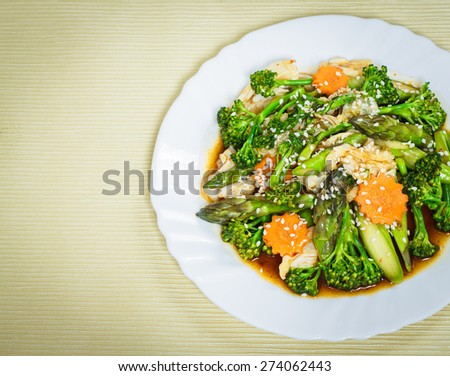 Vegetarian food; stir- fried mixed bio vegetables with soy sauce and sesame seeds on white plate. - stock photo